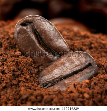 two coffee beans at roasted coffee heap - stock photo