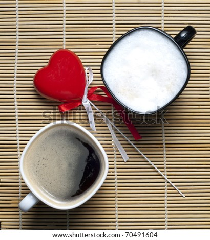 Two coffee cups and a heart - stock photo