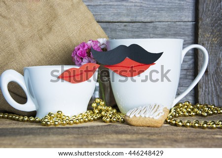 Two coffee or tea cups as kiss couple with red carton kissing lips, heart shape cookies, flowers and a note for text. Romantic date, invitation, sweet wish concept. Selective focus, toned image - stock photo