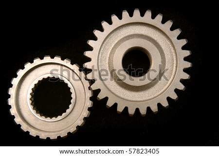 Two cogwheels together on dark surface - stock photo