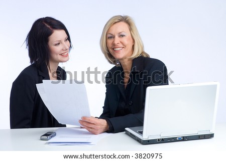 two colleagues are discussing the work, laptop standing on the desk