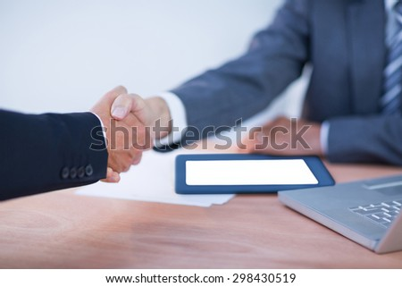 Two colleagues businessmen shaking hands at the office - stock photo