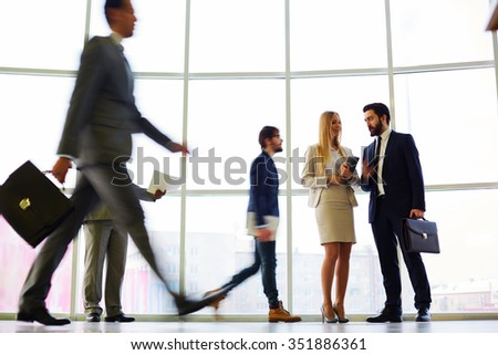 Two colleagues communicating in the hall among other business people - stock photo