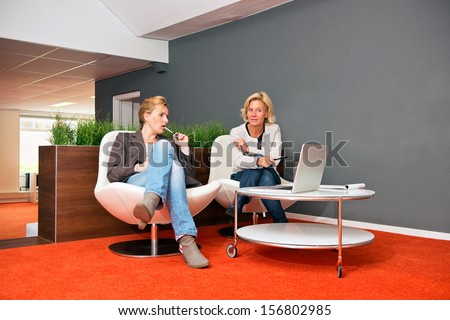 Two colleagues discussing a project in an informal office setting, with laptop, notes and both women casually dressed - stock photo