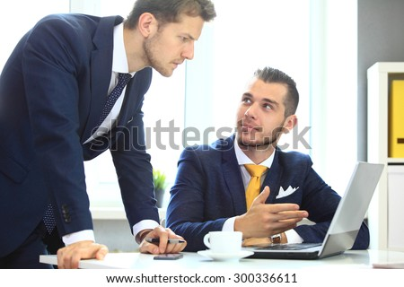 Two colleagues discussing data on laptop - stock photo