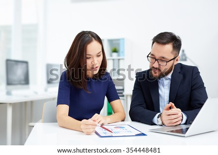 Two colleagues discussing paper at meeting - stock photo
