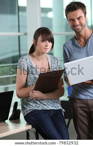 Two colleagues in office with laptop computer