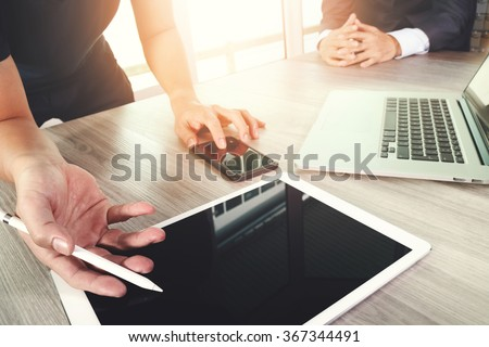 two colleagues interior designer discussing data and blank screen digital tablet and computer laptop with smart phone on wooden desk as concept - stock photo