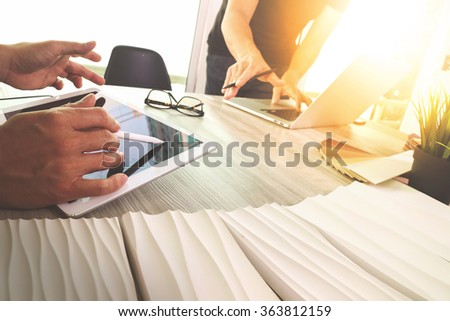 two colleagues interior designer discussing data and digital tablet and computer laptop with sample material on wooden desk as concept - stock photo
