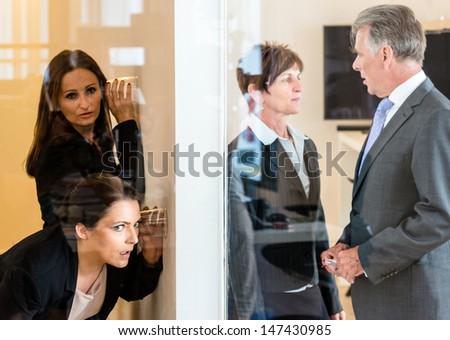 Two colleagues listening with a glass to the wall of the next office room where a man and a woman discuss their matters. Concept for eavesdropping, secrecy or curiosity - stock photo