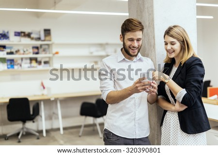 Two colleagues smiling while looking at the phone in a beautiful office - stock photo