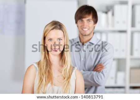 two colleagues standing one behind the other - stock photo