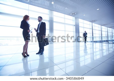 Two colleagues talking at business center with busy manager on background - stock photo