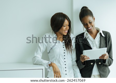 Two colleagues talking while standing about the contents on a tablet pc in a well lit office close to the window - stock photo