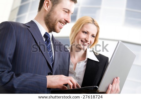 Two colleagues using lap-top near an office centre