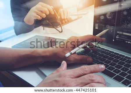 two colleagues website designer discussing data and digital tablet and computer laptop with  graphics design diagram on marble desk as concept, sun flare effect - stock photo