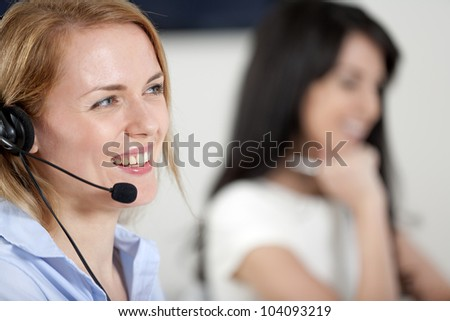 Two colleagues working in a busy call centre office. - stock photo