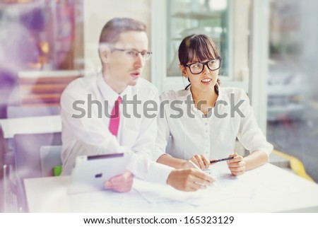 two colleagues working on project (focus on woman) - stock photo