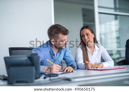 Two colleagues writing something on a paper.