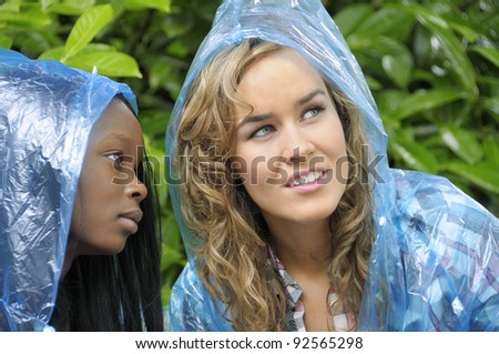 Two college friends in raincoats looking up at the rain clouds in the sky. - stock photo