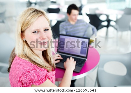 Two college students having fun studying together, using a laptop computer on campus, between classes (shallow DOF, color toned image) - stock photo