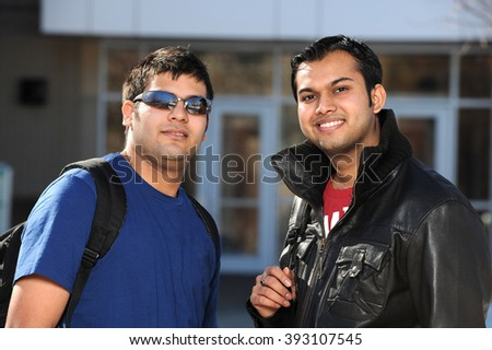 Two college students with backpacks outside building