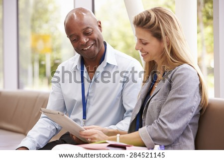 Two College Tutors Looking At Digital Tablet - stock photo