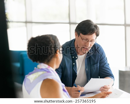 Two collegues working together in a office - stock photo