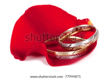 Two color (gold and silver) wedding rings on a red petal of a rose - stock photo