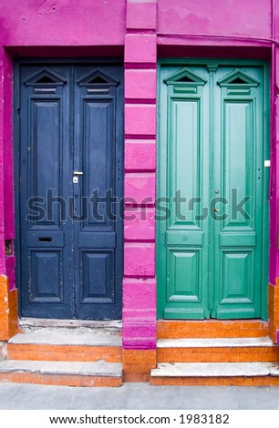 Two colored apartments doors with green, blue, pink and orange color - stock photo