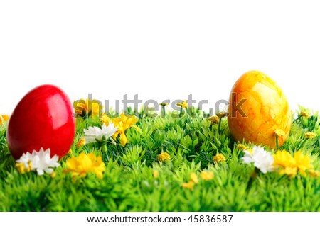 Two colored eggs on grass isolated on white background - stock photo