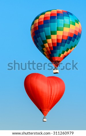 Two colored hot air balloon flying in the blue sky - stock photo