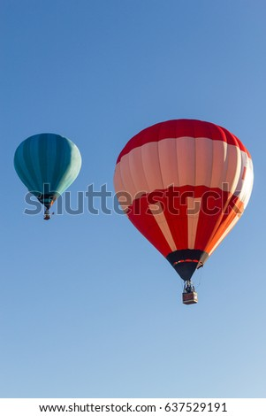 Two Colored hot air balloons flying in a blue sky