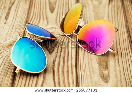 two colored sunglasses close up on the wooden background. horizontal - stock photo