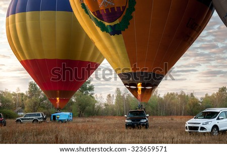 Two colorful air balloons taking off in field at sunrise - stock photo