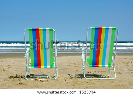 Two colorful beach chairs on the ocean shore - stock photo