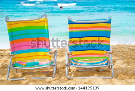 Two colorful beach chairs under by the ocean with sunscreen, with couple in the ocean