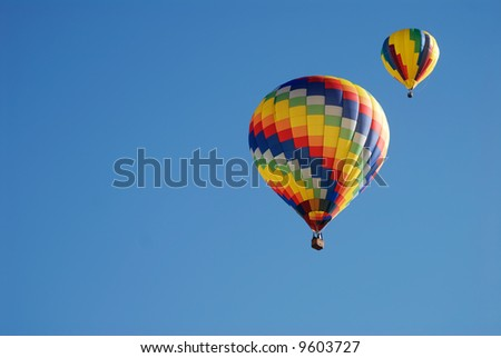 Two colorful hot air balloons floating in the sky