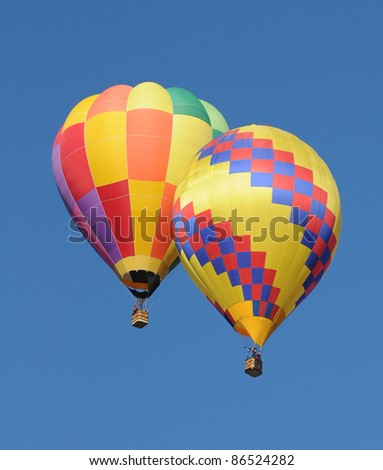 Two colorful hot air balloons floating next to each other