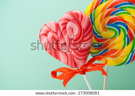 Two colorful lollipops over cyan background. - stock photo