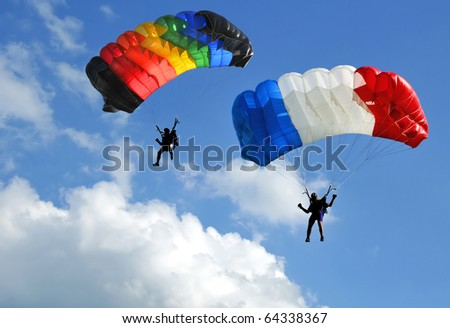 Two colorful parachutes on blue sky.