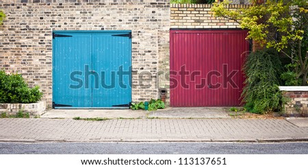 Two colorful red and blue garage doors - stock photo