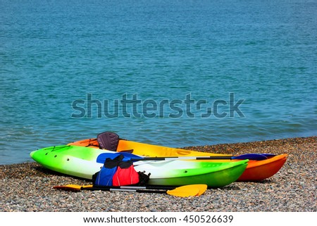 Two colorful sea kayaks with paddles and life jackets on stony beach