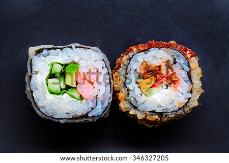 Two colorful sushi on black with copy space - stock photo