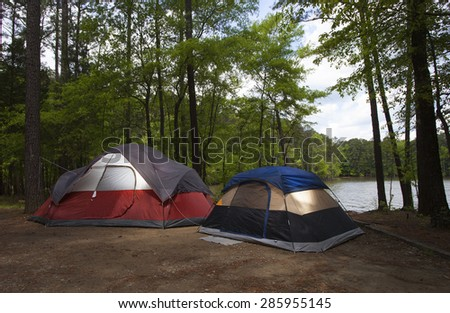 Two colorful tents pitched next to a lake just before sunset - stock photo