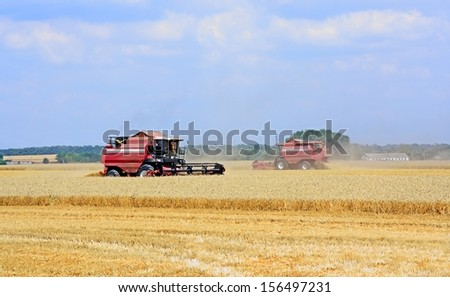 Two combine harvester working in a field - stock photo