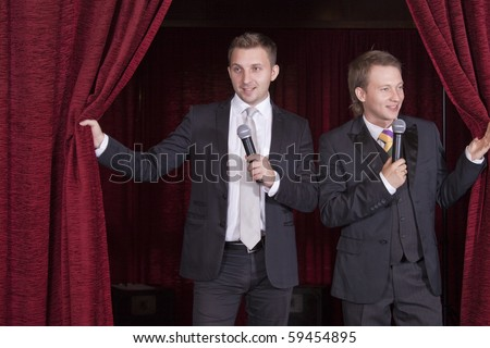 two comedian actors with microphones on stage