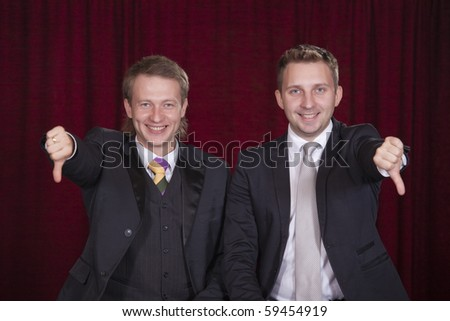 two comedians holding thumbs down on the stage - stock photo
