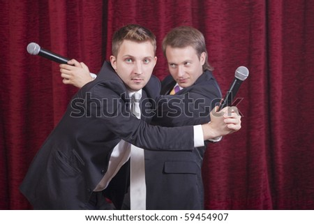 two comedians with microphones acting on the stage - stock photo