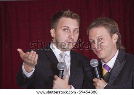 two comedians with microphones on the stage - stock photo
